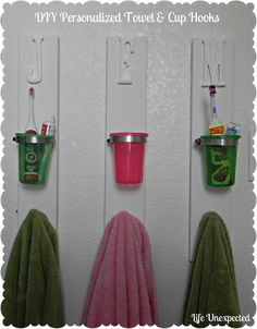 DIY Towel Hook with Toothbrush/toothpaste cup. Perfect! Each kid has a place for their necessities and you can WASH those cups out so they don't get nasty :)