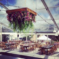 Amazing clear marquee wedding with stunning floral hanging chandelier. Tables provided by us.