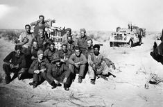 A group of Long Range Desert Group men pose for a photograph in front of their vehicles, having become the first 8th Army unit to cross the Tunisian border. At this time, LRDG patrols were being tasked by Montgomery to reconnoitre the 'going' in southern Tunisia, in case the 8th Army had to bypass the strongly held Mareth Line.