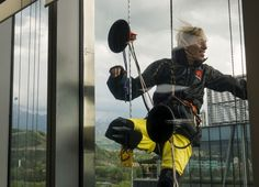 """French climber Alain Robert, also known as """"Spiderman,"""" is seen through a window as he scales the 162-meter (531-foot) Esentai Tower in Almaty, Kazakhstan, on April 23. (Shamil Zhumatov/Reuters)"""