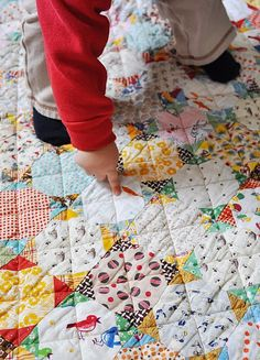 a seriously cute quilt being admired by a seriously cute toddler