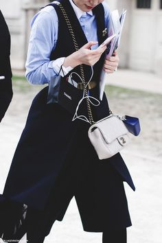 Vest with a blue oxford and a white Chanel bag.
