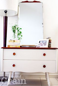 Based in Brisbane, With the Grain lovingly hand restores furniture to create beautiful, functional, statement pieces to complement your home.    Each piece is unique and we also do bespoke items on request.    Made of solid wood, the dresser is very sturdy. It has beautiful brass handles, a full length mirror and striking feet. The top has been stained walnut (with a satin finish) and the bottom is painted in Aged White (Blake & Taylor Furniture Paint) and finished with a satin varnish…