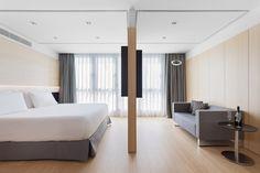 Plano conjunto de la zona de dormitorio y el salón con televisión de la habitación piloto del nuevo hotel del Grupo Hotusa en la Ronda Universitat de Barcelona
