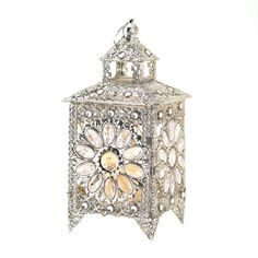 Enjoy the sparkle of this ornate tabletop candle lantern. Faceted jewels set inside luxurious silvertone filigree dazzle when your favorite candle is lit inside. There is nothing common about this enchanting treasure that will illuminate any room.