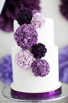 "White tiered wedding cake with multi-shade purple ""pom poms"""