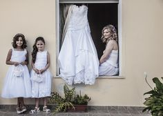 Bride posing with her little bridesmaids and her wedding dress. Orthodox wedding in Chania, Crete. Photography by Shoothebride.