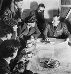 Cecil Beaton photograph of an RAF bomber crew being debriefed by the squadron intellgence officer on their return from a night raid over Germany, 1941.