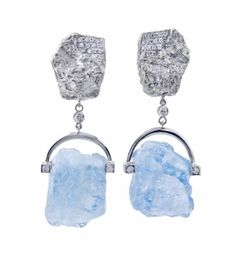 """18kt white gold earring featuring rough Aquamarine crystals which are semi prong set with an inverted """"U"""". There are round brilliant Diamonds set at the b"""