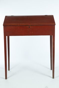 """PENNSYLVANIA SCHOOLMASTER'S OR CLERK'S DESK. Nineteenth century, pine. Slant front with interior drawers and pigeonholes, and on tapered legs. Old red paint. 47""""h. 37.5""""w. 25""""d."""
