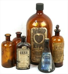 A variety of antique apothecary amber glass bottles. To include; Blood Life 5 gallon, Standard Laundry Bluing 12 ounces, UpJohn 1 gallon Mercresin (includes glass stopper), and three unmarked antique amber glass bottles.