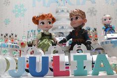 """Com o primeiro nome em comum, e colocado em um painel, as três irmãs donas dessa festa de aniversário com tema """"Frozen"""" tiveram seus segundos nomes representados em cima da mesa do bolo"""