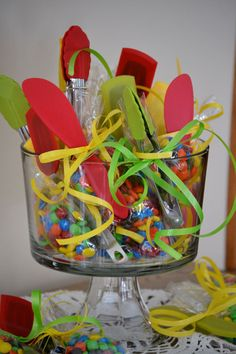Party favors for M bridal shower.  Bright colored kitchen utensils tied with bags of M.