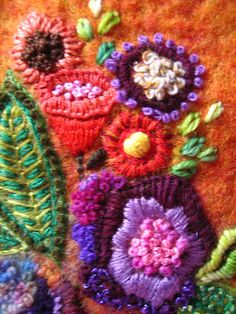 Needle felting embellished with seed beads and fibers.