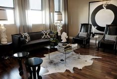 modern chic living room with black modern sofa, black Thomas Paul flock silk pillows, black leather wingback chiars with nailhead trim, ivory cowhide rug, Barcelona Cocktail table, Eileen Gray accent table, Arteriors home glossy black Lola accent tables and taupe walls paint color.
