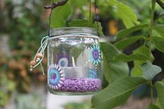 With babyfood jars. Would be great in trees or patio umbrella.