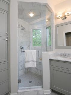 Gray Bathroom with bathroom cabinets painted Benjamin Moore Fieldstone Gray paired with white carrara marble countertops and polished nickel faucets. Gray bathroom mirror with polished nickel double sconces and floor to ceiling gray built-in bathroom cabinets. Seamless glass shower with marble shower surround, marble bench and marble mosaic tile shower floor.