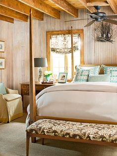 if you love the cozy look of wood but want to avoid a cabin-like look, incorporate a sophisticated color, such as the soft aqua and traditional bedding and accessories.
