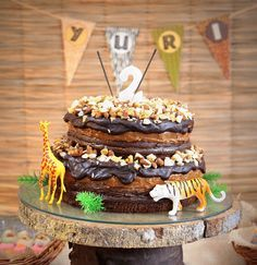 Animal Safari Birthday Party Cake - This is called a layered 'naked' cake, and it lends itself perfectly to the rustic safari-style decorations. Decorate with sparklers, a number candle, loads of nuts and some cute plastic play animals!
