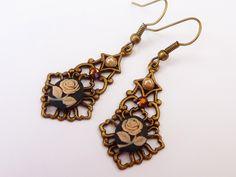 Diese romantischen Ohrringe bestehen aus antikgoldfarbenen Messingornamenten und sind verziert mit kleinen Rosen-Gemmen in rosa-schwarz und braunem...