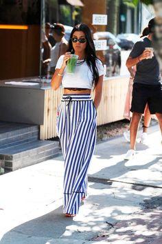 Kourtney Kardashian apostou em uma caça com listras verticais azul e combinou com cropped branco.
