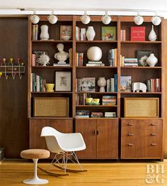 The den's built-in walnut bookcase and oversize track lighting are original to the house and required only a little cleaning to make them shine. The homeowners used the stage to display a number of new and vintage collectibles, including Jonathan Adler ceramics, an Eames rocker, and a vintage Saarinen Tulip side table with the original upholstered top.