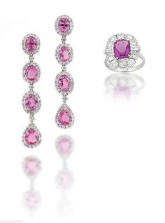 AN 18 CARAT WHITE GOLD PINK SAPPHIRE AND DIAMOND RING AND MATCHING EAR PENDANTS. Set with a rounded rectangular-cut pink sapphire to a brilliant-cut diamond cluster surround with tapered baguette-cut diamond shoulder accents, raised on a polished hoop; together with similarly-set ear pendants ensuite, finger size M and 5.4cm long, each with London hallmarks for 18ct gold