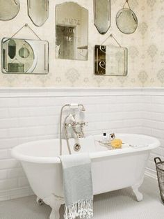 Vintage mirrors over a claw tub in bathroom
