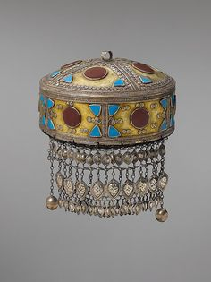 Headdress,  late 19th–early 20th century;   Central Asia or Iran.  Silver, fire-gilded with gallery and twisted wire decoration, flat cut turquoises or enamel and carnelians, silver chains, embossed pendants and bells with quilted cotton lining in interior.