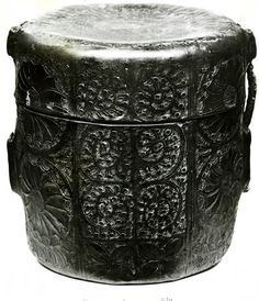Cylindrical case of moulded leather; two vertical loops on each side for straps; incised and stamped decoration in vertical panels of floral scrolls and large whorls in pairs; formerly contained chalice and paten.