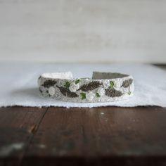 Ce bracelet manchette a belles roses blanches et de fougères verts foncés à la main brodé sur lin naturel doux, il a un mousqueton argent fermoir et chaîne de rallonge et se termine par un petit pompon vert foncé. Parfait pour le printemps !  Taille : Il sadapte confortablement une taille de poignet entre 6 et 7,25 pouces. Chaque bracelet est faite pour sadapter à une variété de tailles de poignet et de souplesse avec comment équipée ou en vrac, vous souhaitez porter. La partie de tissu du…