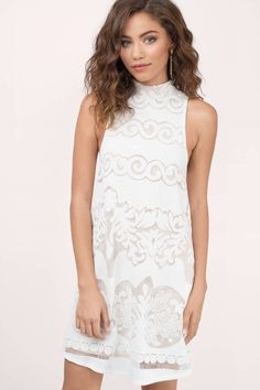 Gorgeous white shift dress with detailed pattern. Pair with statement jewelry for your next night out.