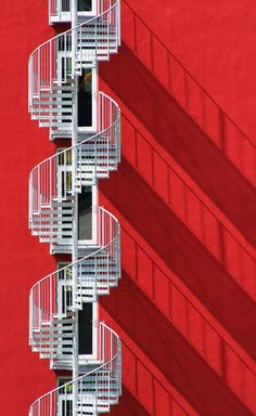 Adore the shadow that this spiral fire escape casts onto the bright red wall. Genius.