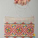El clutch de tela de lino tiene el forro con el bolsillo. La asa está creada de cadenita de metal. La superficie de clutch artesanal bonito está decorada con el bordado en punto de cruz. El bolso...