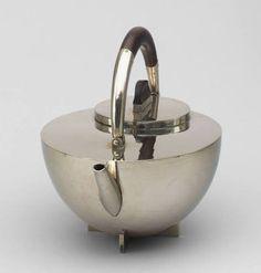 "Marianne Brandt (German, 1893–1983) Teapot Manufacturer: Bauhaus Metal Workshop, Germany Date: 1924 Medium: Nickel silver and ebony Dimensions: .a: 7 x 9"" (17.8 x 22.8 cm) .b: 3 1/4"" (8.3 cm) .c: 2 1/8 x 3 1/8"" (5.4 x 8 cm) Credit Line: Phyllis B. Lambert Fund MoMA Number: 186.1958.1a-c"