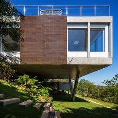 O projeto da Casa Jatobá, assinado pelo escritório Gesto Arquitetura, tira partido da declividade do terreno. Assim, o corpo dos dormitórios repousa sobre o pilar de concreto em formato de V. O painel ripado de madeira garante a privacidade da suíte do casal