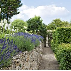 Garden with a stone retaining wall, topiary and paved path which leads the eye to a statue raised on a plinth.