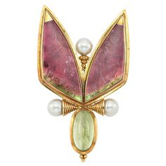 18k Gold, Watermelon Tourmaline, Cabochon Tourmaline and Cultured Pearl Brooch, Elizabeth Gage. The stylized butterfly centering one oval cabochon tourmaline, joined by 2 pearls capped by ribbed gold, topped by watermelon tourmaline wings, all within gold frames, backed by white gold and centering a pearl, supported by tapered gold rings.
