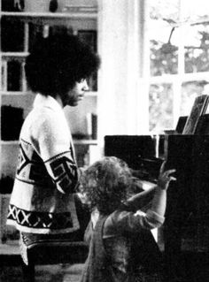 A very young Prince at someones home playing the piano and a kid listening to him.