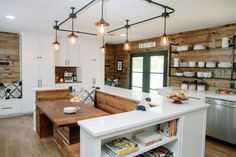 The large eat-in kitchen is efficiently laid out and balanced with cabinets on either end and plenty of storage options. The French doors are updated and the walls throughout are covered in dark-stained shiplap. Track lighting outlines the rectangular shape of the dining set up with built in bench seating.
