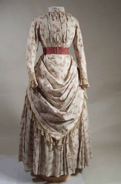 1887-1889 Cream tabby weave wool printed w/ sprays of berries in pink, green & blue. 2- piece. Lined w/ white cotton satin. Centre front fastening w/ buttons. Narrow standing collar. **Watch pocket attached to left front at bust level.** Sleeves w/ turn-back cuff stitched to falling cuff & lace. Skirt closes centre back. Draped overskirt edged w/ lace. Pleated band at waist w/ pleated bow centre front. Underskirt w/ channels for boning. Pocket in right side seam.
