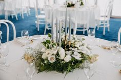 DY.o events (aka Duo)  Grey taper candles in gold candle holders. Modern, timeless wedding round table design. Floral table centre piece.