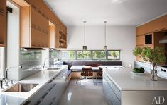 kitchen features an Eames table by Herman Miller, Just Scandinavian chairs, and custom-made glass pendant lights by Deborah Czeresko