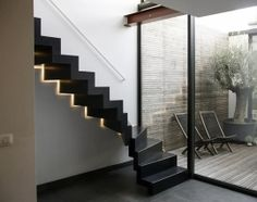 Zwarte stalen trap met kwartdraai en strakke leuning