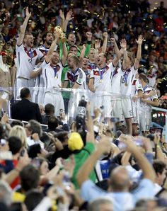 Germany's Shkodran Mustafi holds up the World Cup trophy as the team celebrates their 1-0 victor over Argentina after the World Cup final soccer match between Germany and Argentina at the Maracana Stadium in Rio de Janeiro, Brazil, on July 13, 2014.