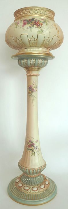 A Royal Worcester Blush Ivory Porcelain Jardiniere on Pedestal, 1899, the cauldron shape jardiniere leaf enriched and semi-gadroon printed and painted with sprays of flowering thistles and asters, 26.5cm high, on a slender swept stem delicately fluted and similarly decorated, on cabochon moulded swept circular base.