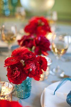 Centros de mesa bajos con flores rojas y frascos azules. www.florama.mx