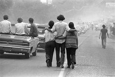 Credit:  © Baron Wolman / www.reelartpress.com Arm-in-arm a procession of festival-goers make their way to Woodstock.
