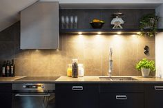 A limestone splashback colors the wall behind the fitted cabinets which hide away an integrated fridge-freezer and dishwasher.
