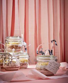 Ingrédients pour biscuits disposés en couches dans des bocaux en verre, avec une note manuscrite et un emporte-pièce fixés dessus.